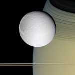 Icy Dione, one of Saturn's moons, enriched by the tranquil gold and blue hues of Saturn. NASA