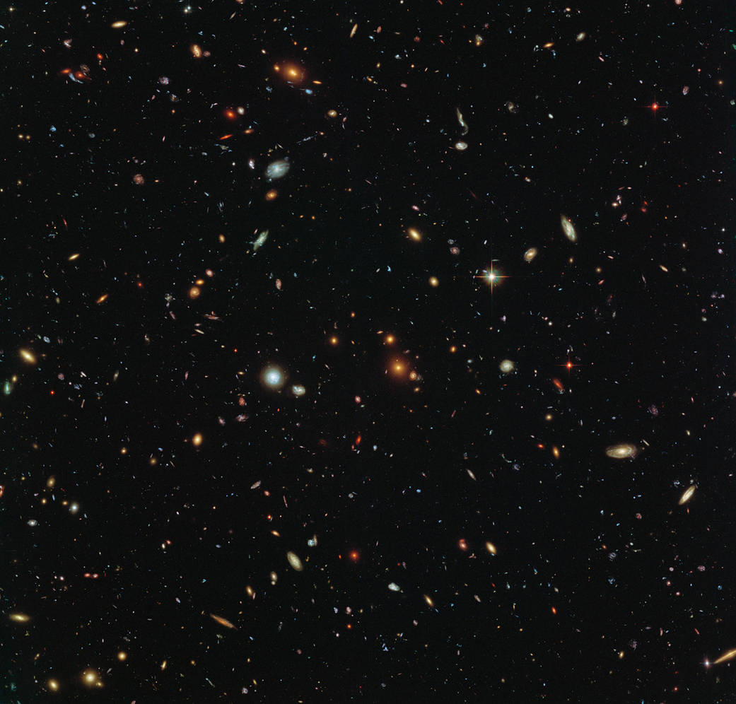 Peering deep into the early Universe, this picturesque parallel field observation from the NASA/ESA Hubble Space Telescope reveals thousands of colourful galaxies swimming in the inky blackness of space. A few foreground stars from our own galaxy, the Milky Way, are also visible. In October 2013 Hubble's Wide Field Camera 3 (WFC3) and Advanced Camera for Surveys (ACS) began observing this portion of sky as part of the Frontier Fields programme. This spectacular skyscape was captured during the study of the giant galaxy cluster Abell 2744, otherwise known as Pandora's Box. While one of Hubble's cameras concentrated on Abell 2744, the other camera viewed this adjacent patch of sky near to the cluster. Containing countless galaxies of various ages, shapes and sizes, this parallel field observation is nearly as deep as the Hubble Ultra-Deep Field. In addition to showcasing the stunning beauty of the deep Universe in incredible detail, this parallel field — when compared to other deep fields — will help astronomers understand how similar the Universe looks in different directions